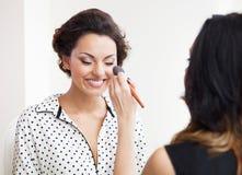 化妆师做补偿年轻美丽的新娘 免版税库存照片