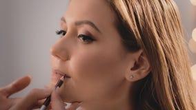化妆师包围并且得出嘴唇的形状有一支铅笔的在一个美好的白种人白肤金发的模型的面孔 股票录像