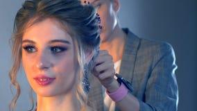 化妆师和美发师在婚礼前准备新娘 有短的时髦的发型的美发师美发师申请构成 股票录像