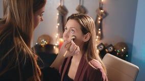 化妆师在一个白种人白肤金发的模型上的面孔把与刷子的一个基础放 构成女商人 在 股票视频