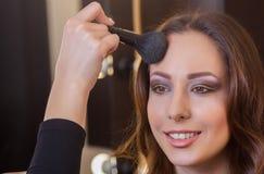 化妆师在一个美丽,深色的女孩上的面孔把粉末放在美容院 库存图片