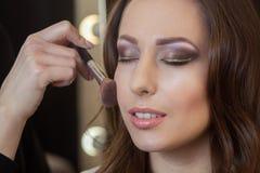 化妆师在一个美丽,深色的女孩上的面孔把粉末放 免版税库存照片
