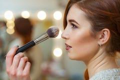 化妆师在一个美丽,红发女孩上的面孔把粉末放在美容院 库存照片