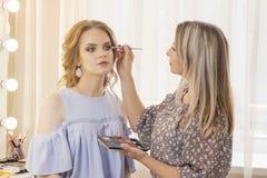 化妆师在女孩模型投入组成 婚姻的构成,自然构成 化妆师在眼皮上把眼影放 免版税库存图片