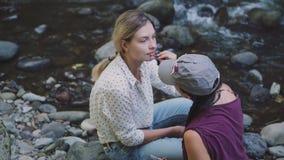 化妆师在异常的情况工作,补偿旅行录影博克,有白肤金发的结辨的头发的一个女孩坐a 股票录像