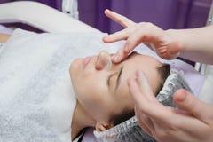 化妆师在润湿面膜以后的Nanost奶油 免版税库存图片