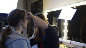 化妆师在演播室绘在棕色长发模型的眼罩 影视素材