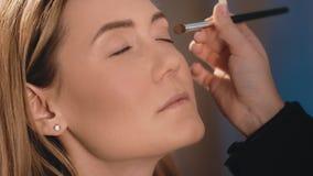 化妆师在眼皮上把明亮的眼影放,有在一个白种人金发碧眼的女人的面孔的一把专业刷子的 股票录像