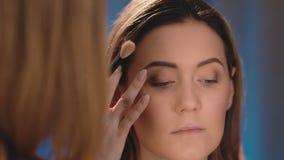 化妆师在眼皮,在一个白种人白肤金发的模型的面孔的一把专业白色刷子上把暗影放 影视素材