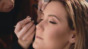 化妆师在眼睛的眼皮上轻轻地把一支黑湿眼线膏放,与在面孔的一把专业刷子  股票视频