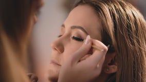 化妆师在眼睛的眼皮上轻轻地把一支黑眼线膏放,与在a的面孔的一把专业刷子 影视素材