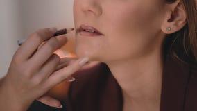 化妆师塑造并且绘更低的嘴唇的形状有一支铅笔的在一个无法认出的白种人的面孔 影视素材