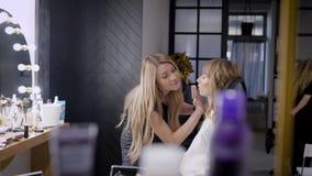 化妆师工作与女性客户在秀丽演播室,应用在嘴唇的香脂,妇女坐 股票视频
