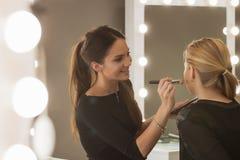 化妆师工作在她的演播室 库存图片