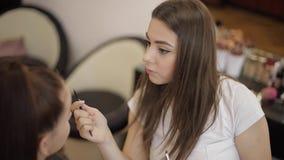 化妆师工作在她的秀丽演播室 申请由专家的妇女组成大师 美丽做艺术家组成  影视素材