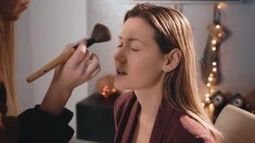 化妆师应用与一把大刷子的粉末于一个白种人白肤金发的模型的面孔 构成女商人 在 股票录像