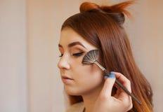 化妆师应用与刷子在女孩` s面孔脸红,结束在美容院的每日构成 免版税库存照片