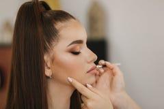 化妆师应用唇膏 构成大师,年轻秀丽红头发人模型的绘的嘴唇的手 组成在过程中 库存照片