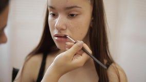 化妆师应用唇膏 构成大师,年轻秀丽红头发人模型的绘的嘴唇的手 组成在过程中 股票录像