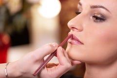 化妆师应用红色口红 E 构成大师,年轻秀丽模型的绘的嘴唇的手 库存照片