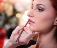 化妆师应用红色口红 E 构成大师,年轻秀丽模型的绘的嘴唇的手 免版税库存照片