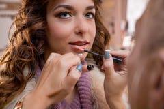 化妆师应用红色唇膏 美丽的表面妇女 构成大师,年轻秀丽模型的绘的嘴唇的手 免版税库存照片