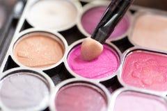 化妆师应用美丽妇女的面孔 免版税库存图片