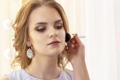 化妆师应用美丽的式样粉末并且脸红与在面孔的大刷子 免版税库存照片