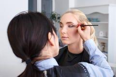 化妆师应用黑眼线膏 图库摄影