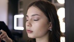 化妆师强加眼影膏最后的接触给模型的眼皮 轻的构成演播室 关闭英尺长度 股票视频