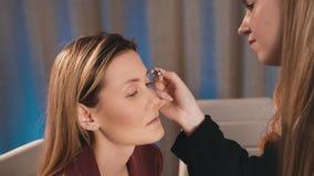 化妆师得出并且导致眼眉的形状有一支铅笔的在一个白种人白肤金发的模型的面孔 构成 股票视频