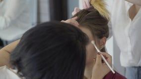 化妆师申请构成于妇女,并且美发师做她的头发 股票视频