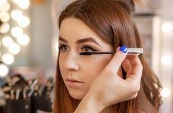 化妆师申请构成并且上色在美容院的染睫毛油睫毛 免版税库存图片