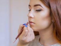 化妆师申请构成并且上色有一把专业刷子的唇膏在美容院 库存照片