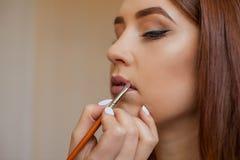 化妆师申请构成并且上色有一把专业刷子的唇膏在美容院 库存图片