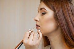 化妆师申请构成并且上色有一把专业刷子的唇膏在美容院 免版税库存照片
