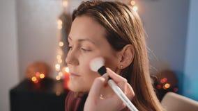 化妆师申请脸红与在一个白种人白肤金发的模型的面孔的一把平均白色刷子 构成事务 影视素材