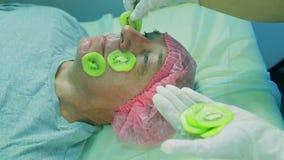 化妆师的妇女的手从人的人去除从小腿猕猴桃的一个面具 股票录像