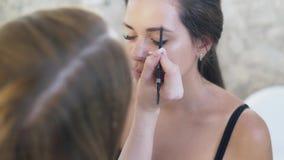 化妆师绘一个客户的眼眉有一支棕色铅笔的 美容院的,化妆师概念 股票录像