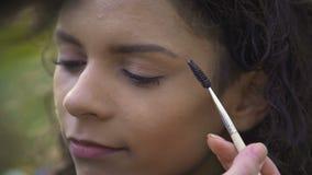 化妆师美丽的年轻女性为射击做准备,提高眼眉 股票视频