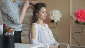 化妆师美发师与模型一起使用 美发师做头发称呼模型 妇女工作一styler与 股票视频