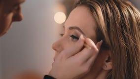 化妆师轻轻地适用于一支黑表面无光泽的眼线膏眼皮,在白种人的面孔的一把专业刷子 影视素材