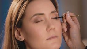 化妆师适用于一支黑眼线膏有一把专业刷子的眼皮在一个白种人金发碧眼的女人的面孔 股票录像