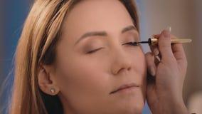 化妆师适用于一支黑眼线膏有一把专业刷子的眼皮在一个白种人金发碧眼的女人的面孔 影视素材