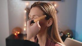 化妆师阴影粉末和大刷子构成在一个白种人白肤金发的模型的面孔 构成女商人 股票录像