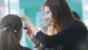 化妆师,工作与美容院的客户的美发师,塑造眼眉 股票录像
