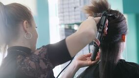 化妆师,工作与美容院的客户的美发师,梳头发-背面图 股票视频