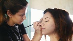 化妆师,工作与美容院,塑造的和上色眼眉的客户的美发师 影视素材