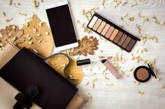 化妆材料、手机和女性袋子在白色桌上与叶子 库存照片