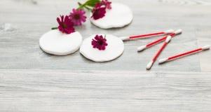 化妆棉花盘和芽 化装棉和拖把,在桃红色长毛绒布料的大块 库存照片